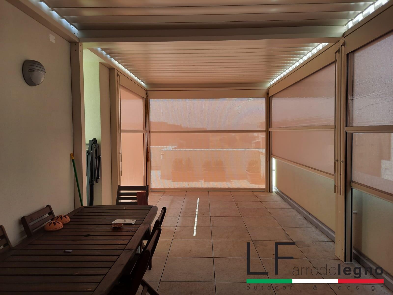 Tende oscuranti a doppio rullo perimetrali montate su una struttura pergola pioclimatica con lamelle orientabili e incluse di illuminazione led