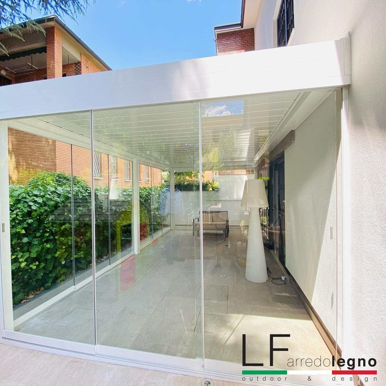 Pergola bioclimatica motorizzata addossabile a parete con lamelle orientabili con chiusure perimetrali in vetro colore bianco