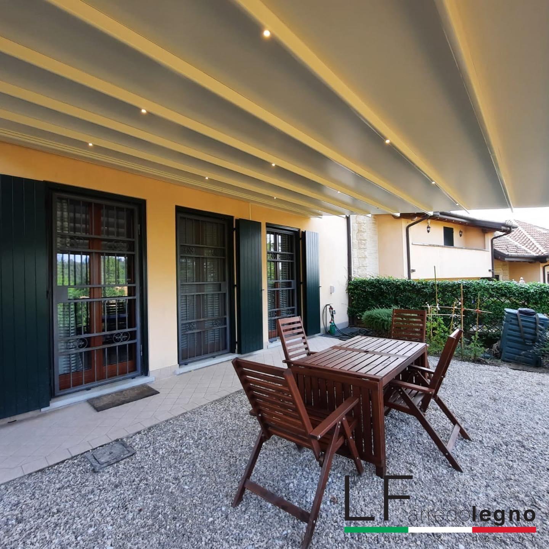 Pergotenda motorizzata struttura colore marrone e telo in PVC colore avorio con luci led incorporate